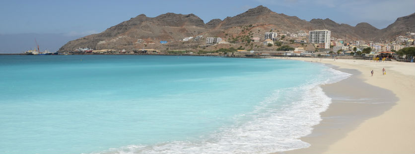 clear light blue water lining sand on a beach with hills in the background