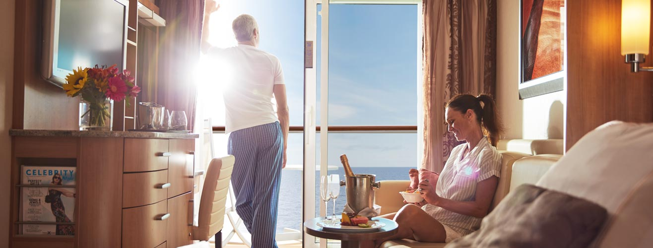 A lady sitting on a couch having fruits and a man standing by the window looking over the sea
