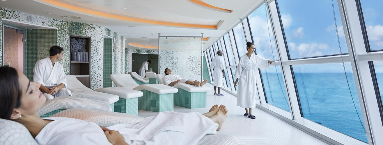 People relaxing in bath robes in a spa room with a sea view